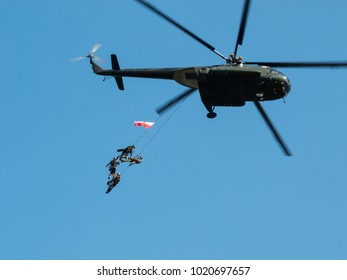 WARSAW, POLAND - SEPTEMBER 13, 2014: Polish GROM Special Forces show off their skills hanging on ropes from a helicopter.