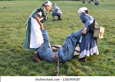Warsaw, Poland - September 15, 2018: Nurses help a wounded Polish soldier. Historic reconstruction of Polish-Soviet war (1919-1921) in Pole Mokotowskie park.