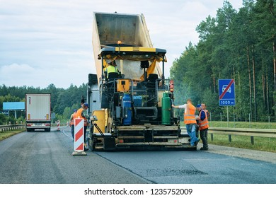 Warsaw, Poland - September 15, 2018: Road paving machine on the road in Poland. Workers at paver finisher.