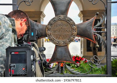 Warsaw, Poland - September 2015: Cameraman shooting military parade from behind the 'Honor i  Ojczyzna' plaque at The Tomb of the Unknown Soldier. Honor Ojczyzna is Polish for Honour and Fatherland