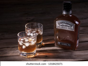 WARSAW, POLAND-DEC 20, 2018: A bottle of Jack Daniel's Gentleman Jack whiskey with filled glasses on a wooden background.