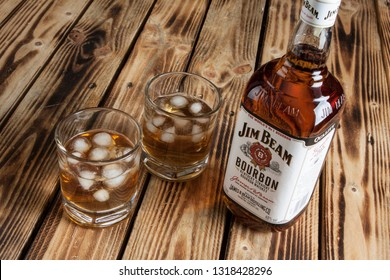 WARSAW, POLAND-DEC 20, 2018: A bottle of Jim Beam bourbon with filled glasses on a wooden background.