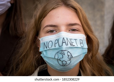 Warsaw, September 2020: Portrait of a girl wearing face protective mask at Youth strike for climate in protest of climate change policy. No planet B sign