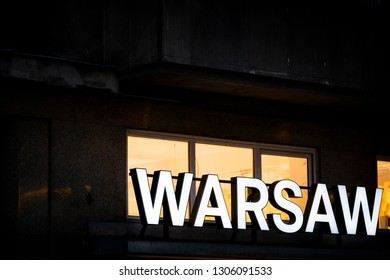 Warsaw sign in the Polish capital against dark backdrop