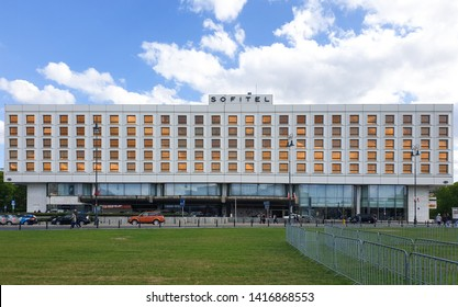 Warsaw/Poland - May 3, 2019:Facade of hotel Sofitel Victoria Warsaw, one of the first Western hotels in the city, built in 1976. Modern architecture, gold windows, green grass and blue sky background