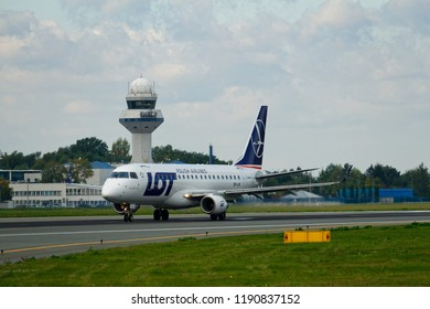 WARSAW/POLAND - SEPTEMBER 22, 2018: View on the Embraer ERJ-175LR of LOT Polish Airlines on runway at Chopin Airport. Control tower in the background