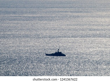 Warship, patrol vessel, coastguard in the Kerch Strait from the Black sea to the Azov sea. Beautiful silvery sea from a bird's-eye view