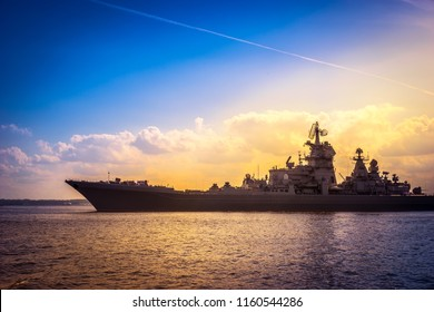 A warship sails to the sea. Rocket cruiser. Military naval forces. Contour of a warship. Protection of maritime boundaries.