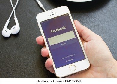 WARSZAWA, POLAND - APRIL 01, 2014: Hand holding iphone with loging in Facebook app. Facebook the largest social network in the world.