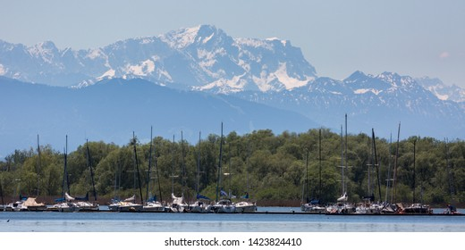 WARTAWEIL, BAVARIA / GERMANY - June 2, 2019: View on Zugspitze mountain. In front a pier with sailboats at Lake Ammersee. Zugspitze is part of the Wetterstein mountain range. Daily trips & excursions.