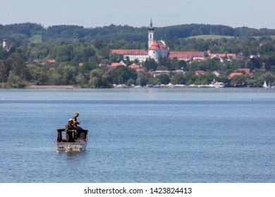 WARTAWEIL, BAVARIA / GERMANY - June 2, 2019: Boat with two fishermen at Lake Ammersee. In the background the Marienmünster Diessen (Dießen; abbey church). Travel destination, beautiful landscape.