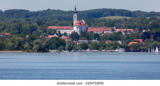 WARTAWEIL, BAVARIA / GERMANY - June 2, 2019: Scenic panorama view of the Marienmünster Dießen (Diessen; abbey church). Lake Ammersee in the foreground. The construction of the church started in 1720.