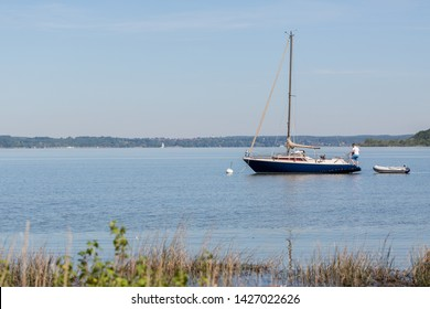 WARTAWEIL, BAVARIA / GERMANY - June 2, 2019: View on blue and white colored sailboat at Lake Ammersee. Sailing is a common activity in the upper bavarian five-lakes-region.