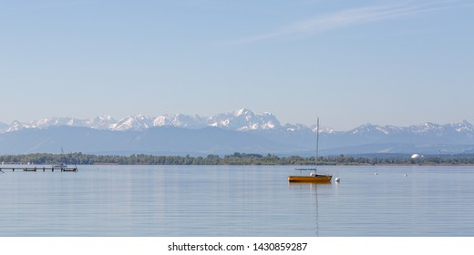 WARTAWEIL, BAVARIA / GERMANY - June 2, 2019: Panaorama view of Lake Ammersee with orange sailboat and Wetterstein Mountain Range in the background . The snow-capped peak in the middle is Zugspitze.