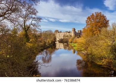 Warwick castle on the river Avon warm autumn day fall colours, Warwick, Warwickshire, England, UK, November 2017
