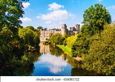 Warwick, UK. Avon river in Warwickshire with autumn forest and Castle of Warwick. Popular landmark in UK. Sunny day with cloudy sky