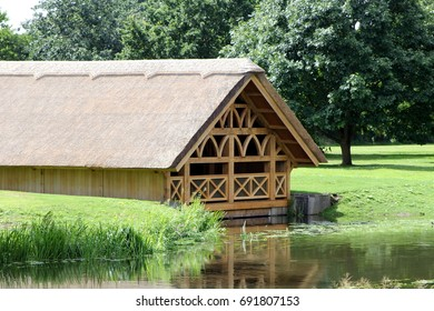 Warwick, UK - July 22 2017: Pretty tudor style wooden framed thatch boathouse in a wood on the edge of a lake or river on a sunny day