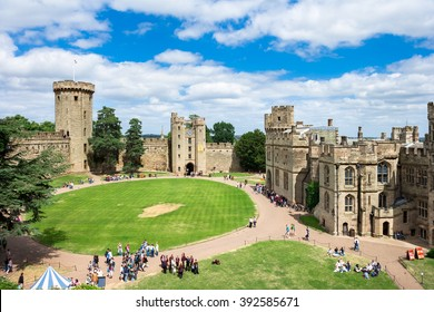 Warwick, United Kingdom - June 21, 2006: View of the Medieval castle tower and gatehouse from within the castle gardens and people enjoying the setting, Warwick, Warwickshire