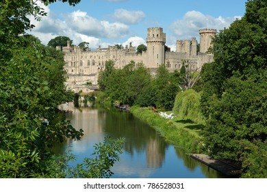 WARWICK, WARWICKSHIRE, ENGLAND - JULY 10, 2017: Medieval Warwick Castle on banks of the River Avon built in the 14th and 15th centuries in morning sunshine