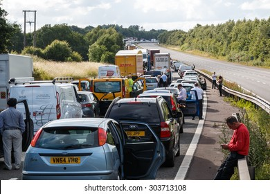 Warwickshire,UK - June 28th 2015:Drivers standing next to lines of queing traffic in a motorway traffic jam after an accident.  This happened on the M40 in England.
