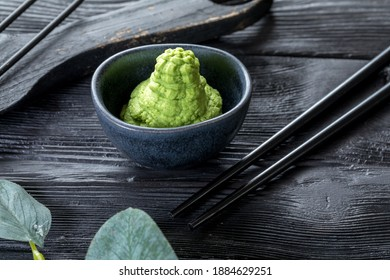wasabi in a ceramic saucepan. Black wooden background and decor.
