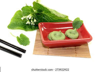 Wasabi with Chopsticks, leaves and blossoms in a red bowl