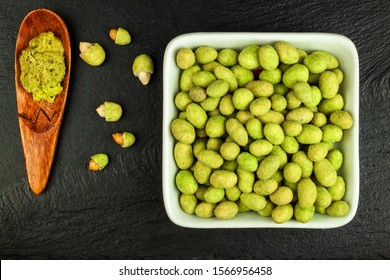Wasabi Coated Peanuts on slate board. Japanese Wasabi Spice. Green wasabi peanuts on a black plate on a dark background.