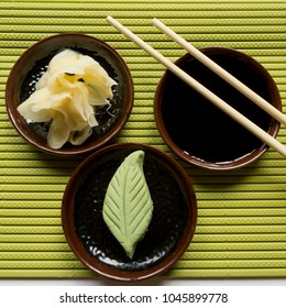 wasabi, ginge and soy sauce sit on green sushi mat