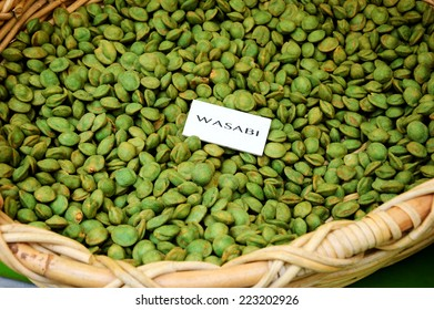 Wasabi peas in wicker basket  for sale at food market. Tag with product name.