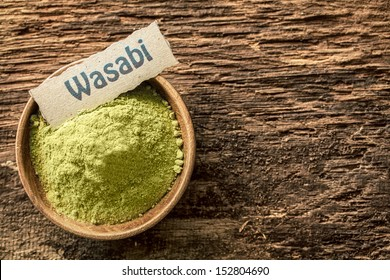 Wasabi, a pungent green Japanese condiment made from the root of the herb Eutrema wasabi, dried and powdered in a bowl standing on a textured weathered surface with copyspace