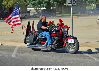 WASCO, CA - SEPTEMBER 6, 2014: Rene Salinas entertains parade watchers with his beautifully decorated red motorcycle during the Festival of Roses highlighting one of the area's major farm products.