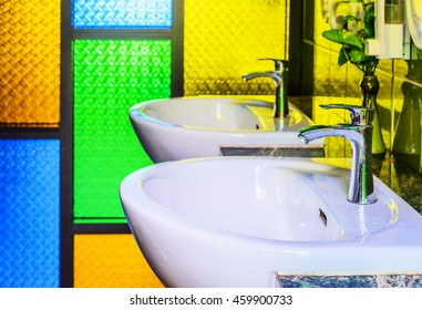 Wash basin in the toilet with colors glass