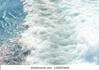 The wash from a boat is seen as white foam against the blue of the sea.
