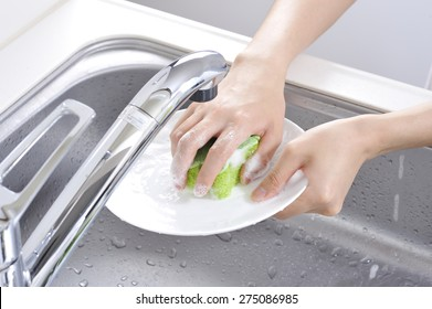 Wash the dishes in the kitchen