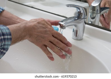 Wash hands on sink with soap and water