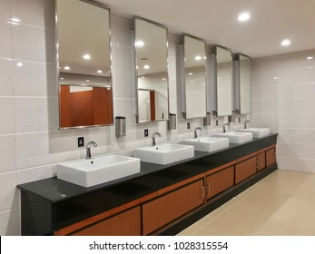 Wash sink and big mirror in public toilet , row of wash basin on wooden counter in restroom