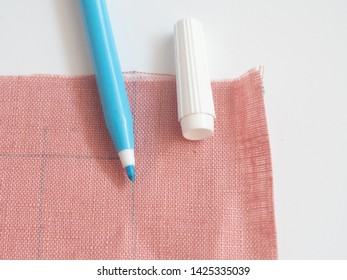 A washable fabric marker on pink linen fabric on white background. Marks on the fabric. Sewing equipment