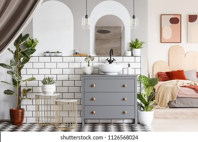 Washbasin on grey cabinet under mirror in open space interior with bed under posters. Real photo