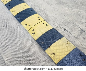 Washboard road. Black and yellow speed bump or speed breaker. Transportation concept.