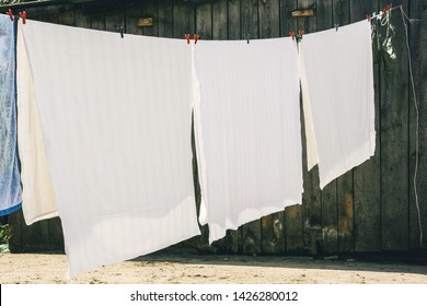Washed bed linen hanging on rope and dry at the yard in the sun