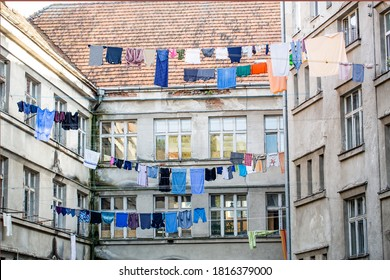 Washed clothes drying outside of an old house. Washed clothes drying. Fresh clean clothes are drying outside. Clothes hanging to dry on a clothes-line. Laundry dryings on the rope.