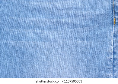 Washed and shabby blue denim with seam texture as background.