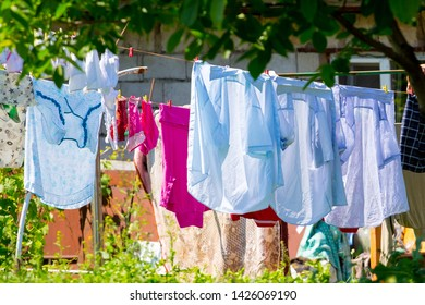 The washed shirts and linen dry on the street in the sunny weather