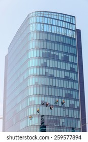 Washers wash the windows of modern skyscrape