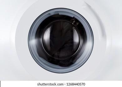 washing black clothes, closed wash machine closeup