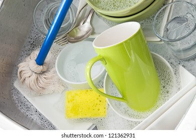 Washing bright dishes in the kitchen sink.