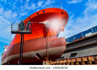 Washing and Cleaning in shipyard Worker in floating dry dock with water jet cleans the shipboard and have movement of people of the ship from sea vegetation before sandblast and paint