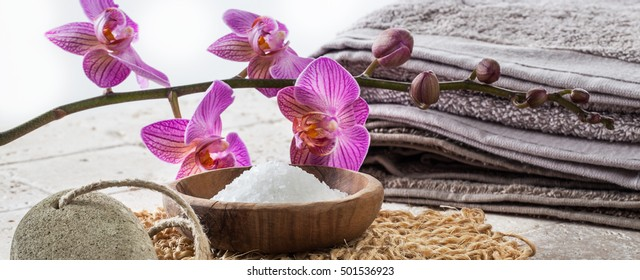 washing up concept with bath salt, pumice stone, cotton towel, loofah mitt and pink flowers for natural softening bath
