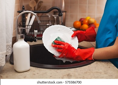 Washing the dishes after a meal - child hands scrubbing a plate with a sponge and rinsing under the water jet, shallow depth