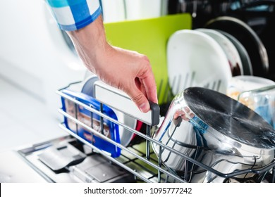 Washing dishes in the dishwasher. The man puts dirty dishes in the dishwasher. Opening and closing the dishwasher. The man cares about the house, does his homework.